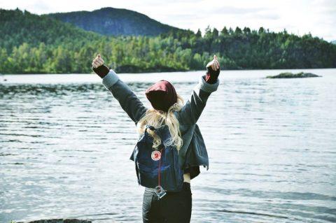 Wanita berdiri di depan danau dan bersorak seolah-olah dia bisa mendapatkan jackpot.